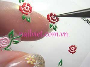 Dùng panh để gắp hoa hồng dán lên móng