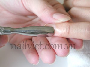 Dùng dụng cụ để đẩy da chết để loại bỏ phần da chết trên móng