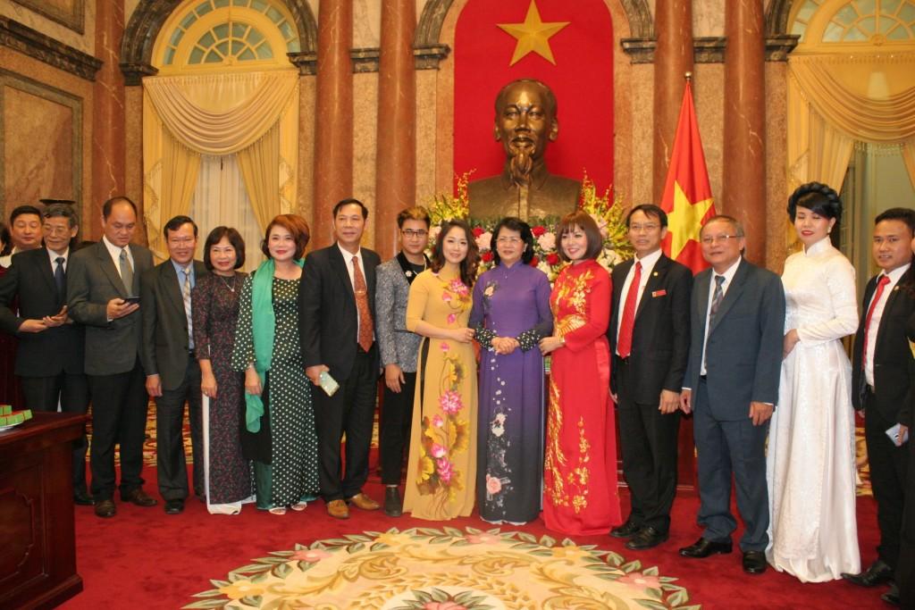 Bà Nguyễn Hải Yến đại diện học viện Winnie áo vàng đứng bên trái phó chủ tịch nước